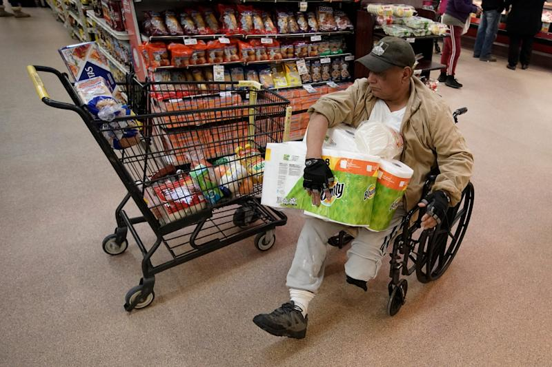A shopper navigates an isle at Northgate González Market on Tuesday, March 17, 2020, in Santa Ana, California. In light of coronavirus concerns, the Northgate market chain opened the store one hour early for seniors 65-years and older and disabled.