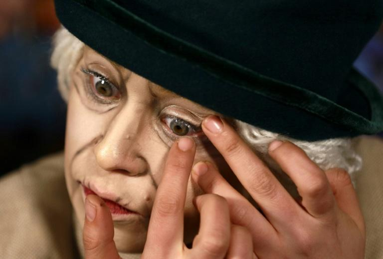 Make-up artist Alaa Bliha applies coloured eye lenses to complete her imitation make-up to resemble Queen Elizabeth II