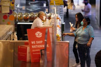 Customers buy goods at the Grand Central Market Monday, Nov. 16, 2020, in Los Angeles. California Gov. Gavin Newsom announced Monday, Nov. 16, 2020, that due to the rise of COVID-19 cases, Some counties have been moved to the state's most restrictive set of rules. The new rules begin, Tuesday, Nov. 17. (AP Photo/Marcio Jose Sanchez)
