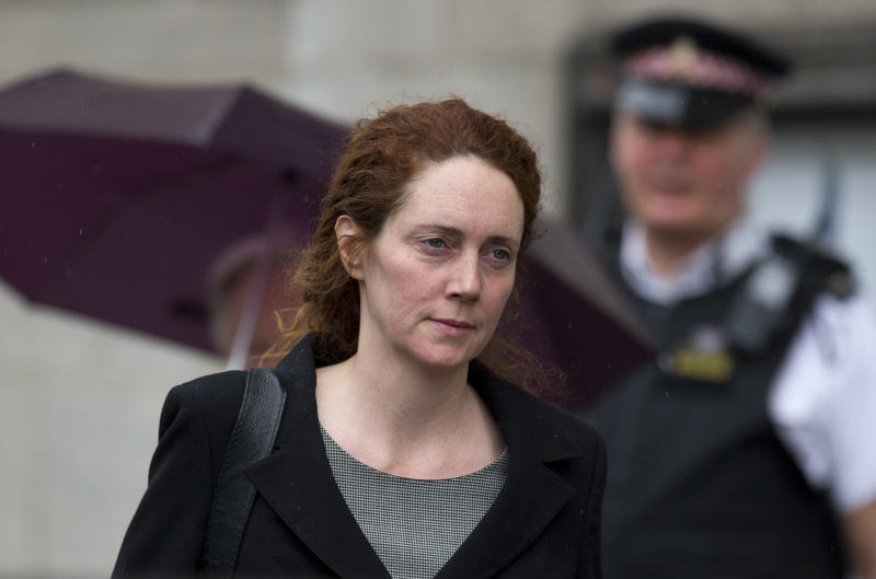 Rebekah Brooks, the former chief of News Corp.'s British newspapers is watched by a police officer as she leaves after attending a hearing in a corruption case at the Old Bailey court in the City of London, Friday, March 8, 2013.  Brooks appeared in court Friday to face charges over alleged conspiracy to bribe a public official to obtain information.  (AP Photo/Matt Dunham)