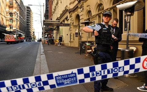 Police gather at the crime scene after a man stabbed a woman and attempted to stab others in central Sydney - Credit: AFP