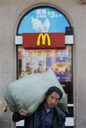 A man carries a sack holding his belongs in front of a McDonald's restaurant at a railway station in Beijing October 23, 2013. REUTERS/Kim Kyung-Hoon