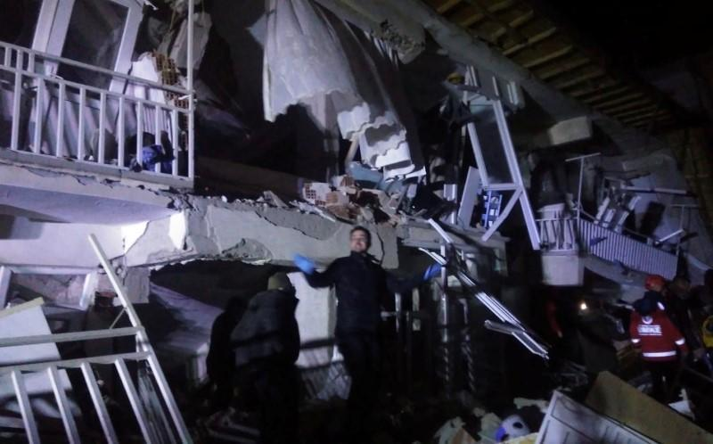 Rescuers are seen outside a collapsed building after an earthquake in Elazig