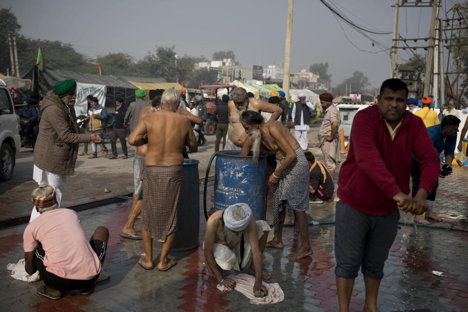 "Protesting farmers bathe at a fuel station along a major highway as they block a major highway during a protest to abolish new farming laws they say will result in exploitation by corporations, eventually rendering them landless, at the Delhi-Haryana state border, India, Tuesday, Dec. 1, 2020. The busy, nonstop, arterial highways that connect most northern Indian towns to this city of 29 million people, now beat to the rhythm of never-heard-before cries of ""Inquilab Zindabad"" (""Long live the revolution""). Tens and thousands of farmers, with colorful distinctive turbans and long, flowing beards, have descended upon its borders where they commandeer wide swathes of roads. (AP Photo/Altaf Qadri)"