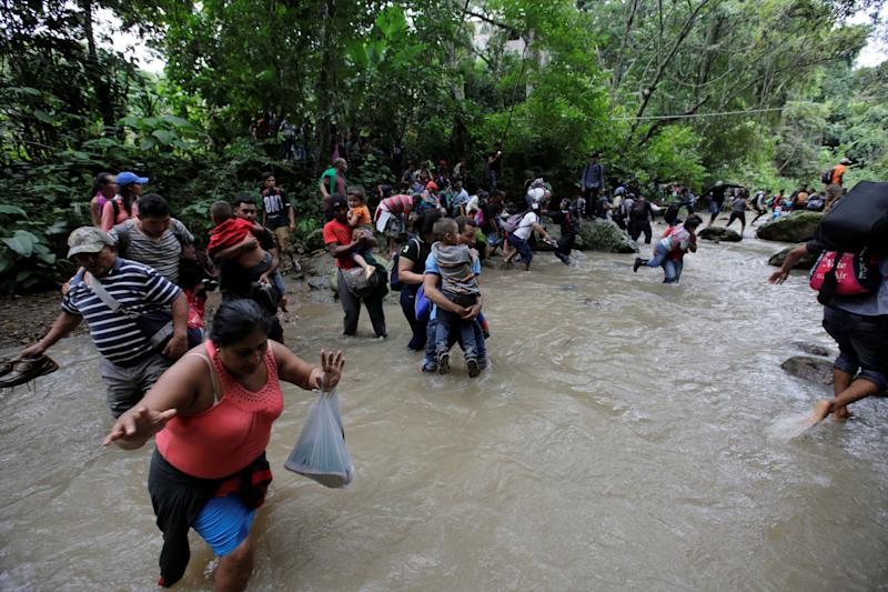 People clutch children and belongings as they wade through currents.