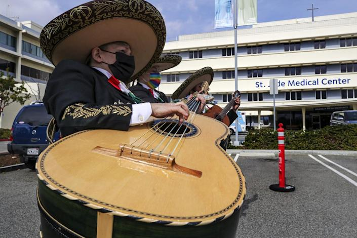 A mariachi band plays a song in a parking lot.