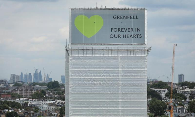 A sign with 'Grenfell Forever In Our Hearts' is displayed on the top of Grenfell Tower, London.