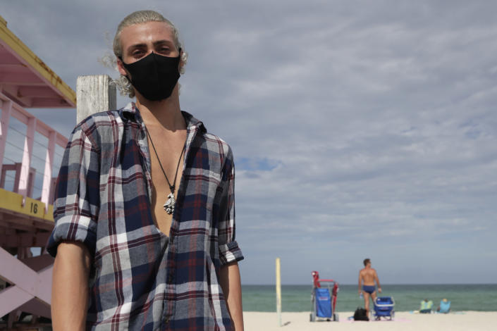 Nivek Divincci wears a protective mask as he poses for a photograph on the beach at Haulover Park during the new coronavirus pandemic, Friday, June 19, 2020, in Miami. Warm weather beach destinations are the most popular vacation searches, with Florida, Myrtle Beach, S.C., San Diego and Key West, Fla., among the top considerations. (AP Photo/Lynne Sladky)