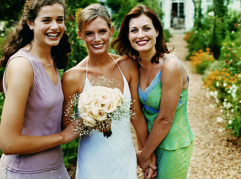 Bride stands with two wedding guests on her wedding day