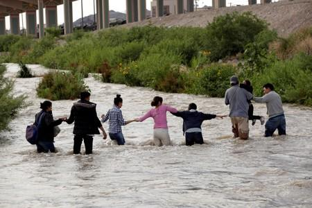 FILE PHOTO: Migrants from Central America form a human chain to cross the Rio Bravo river as seen from Ciudad Juarez