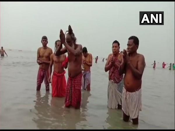 Devotees and hermits take a dip in the Gangasagar river in West Bengal. (Photo/ANI)