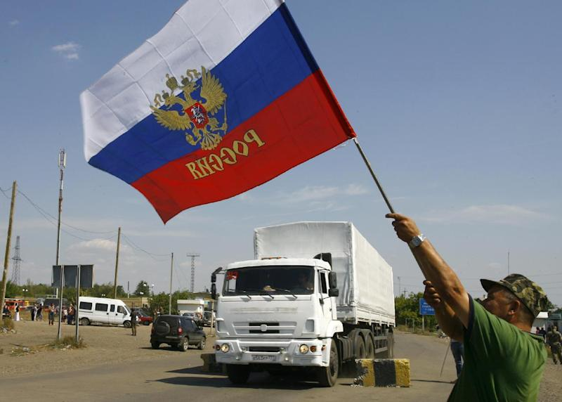 A local resident holds a Russian national flag as lorries, part of a Russian humanitarian convoy cross the Ukrainian border at the Izvarino custom control checkpoint, on August 22, 2014