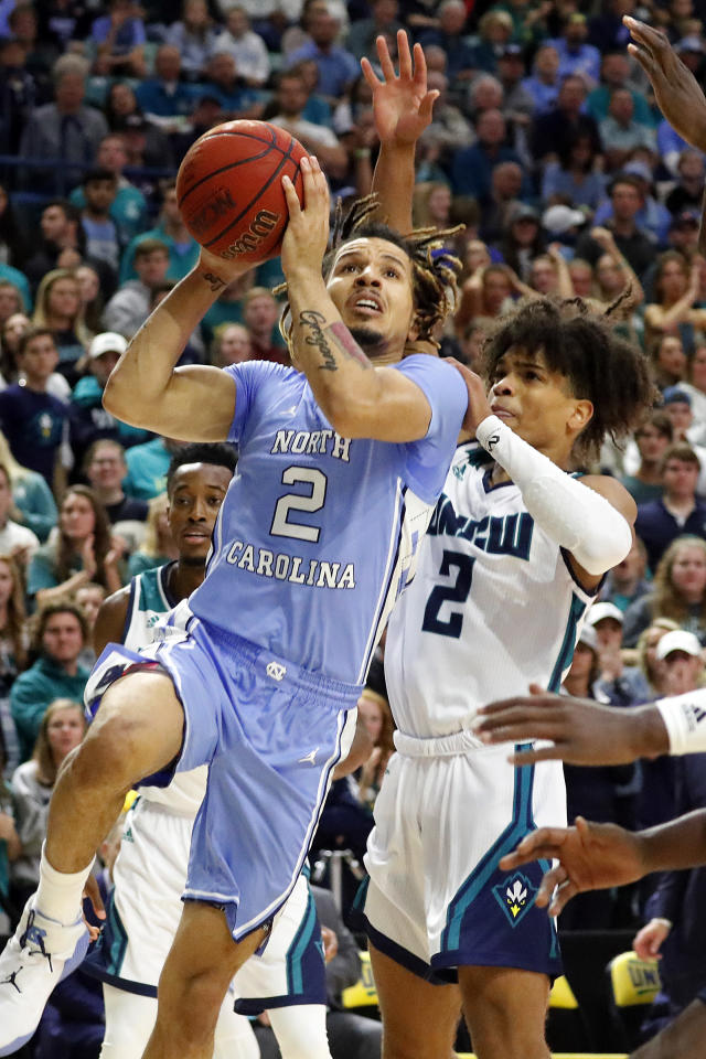North Carolina's Cole Anthony (2) drives the ball past UNC Wilmington 's Shykeim Phillips (2) during the first half of an NCAA college basketball game in Wilmington, N.C., Friday, Nov. 8, 2019. (AP Photo/Karl B DeBlaker)