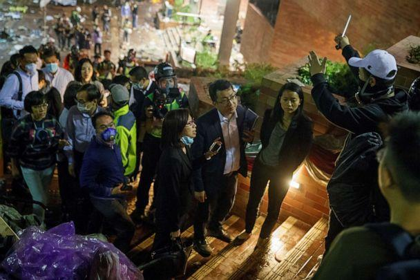 PHOTO: Teachers and relatives negotiate with protesters about the surrender of younger students from the occupied campus of the Hong Kong Polytechnic University that is surrounded by police in Hong Kong, Nov. 19, 2019. (Thomas Peter/Reuters)