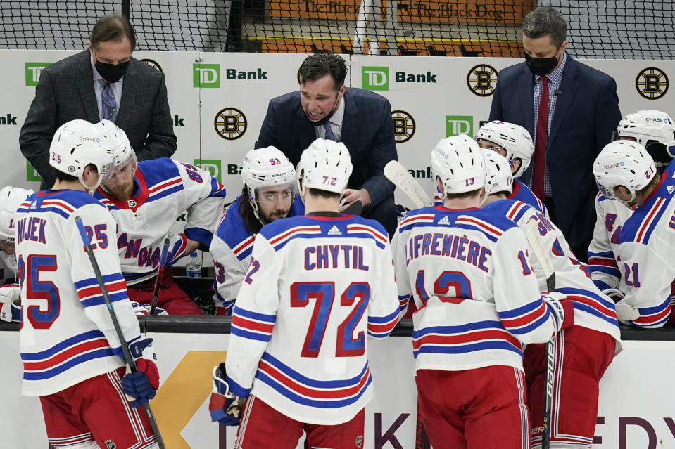New York Rangers coach David Quinn, middle rear, speaks to players during a timeout in the second period of the team's NHL hockey game against the Boston Bruins, Thursday, March 11, 2021, in Boston. (AP Photo/Elise Amendola)