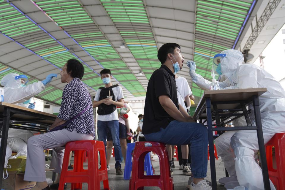 Residents get tested for the coronavirus in a district in Guangzhou in southern China's Guangdong province on Sunday, May 30, 2021. The southern Chinese city of Guangzhou shut down a neighborhood and ordered residents to stay home Saturday to be tested for the coronavirus following an upsurge in infections that has rattled authorities. (AP Photo)