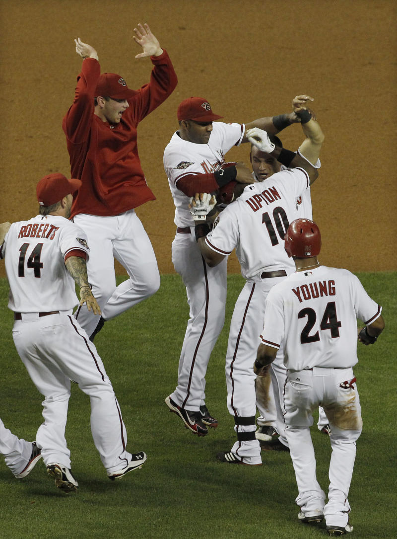 Arizona Diamondbacks' Justin Upton (10) celebrates with teammates,  including Ryan Roberts (14) and Chris Young (24), after Upton's game-winning hit against the Colorado Rockies during the 11th inning of an MLB baseball game Thursday, May 5, 2011, in Phoenix.  The Diamondbacks defeated the Rockies 3-2. (AP Photo/Ross D. Franklin)