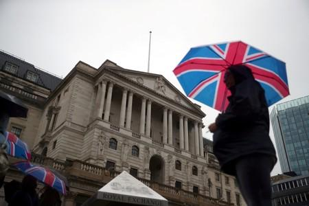 A pedestrian shelters under an umbrella in front of the Bank of England, in London