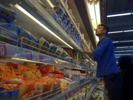 An Iranian employee checks the food shelves at a shopping mall in Tehran