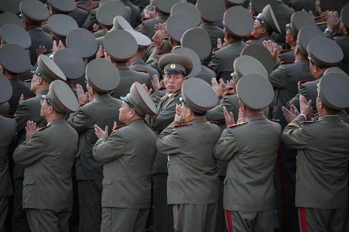 Soldiers applaud the arrival North Korean leader Kim Jong-Un during a mass military parade at Kim Il-Sung square in Pyongyang in October 2015 (AFP Photo/Ed Jones)
