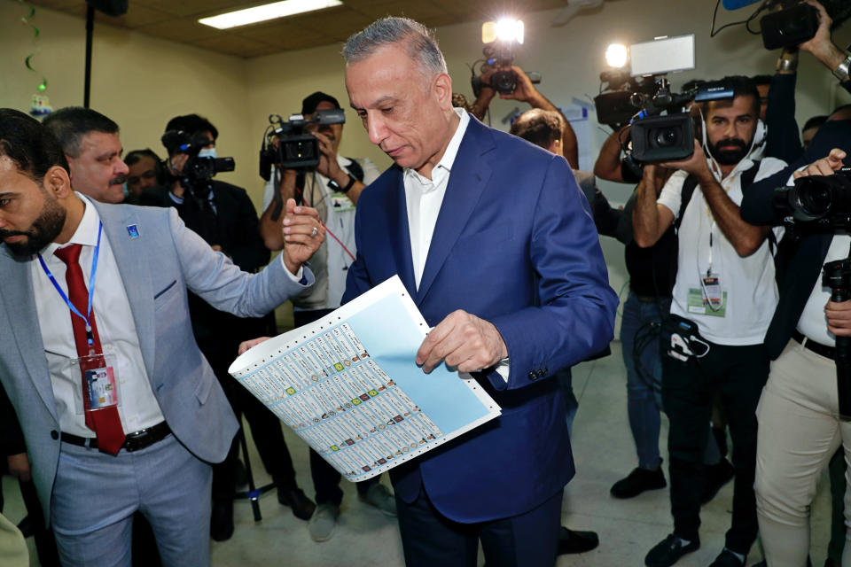 Iraqi Prime Minister Mustafa al-Kadhimi casts his vote during parliamentary elections in Baghdad, Iraq, Sunday, Oct. 10, 2021. Iraq closed its airspace and land border crossings on Sunday as voters headed to the polls to elect a parliament that many hope will deliver much needed reforms after decades of conflict and mismanagement. (AP Photo/Khalid Mohammed)