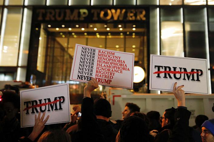 <p>Demonstrators hold signs outside Trump Tower during a protest march against President-elect Donald Trump in Manhattan, New York, U.S. November 9, 2016. (REUTERS/Andrew Kelly) </p>