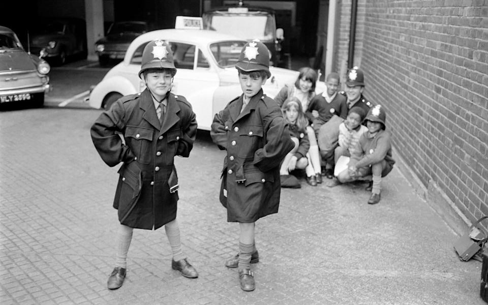 Today they went to the Tooting Police Station, where P.C. Brian Curson of Wandsworth showed them around, they have become his group and come to him for advice, but primarily they run the club themselves. Year old twins Peter and Nigel Nethercote try on new policeman's uniforms which had just arrived at the station. In the background P.C. Curson and the other children. October 1969 Z10506-001 (Photo by Mirrorpix/Mirrorpix via Getty Images) - Getty