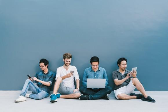 Four young adults sitting on the floor using their consumer electronics
