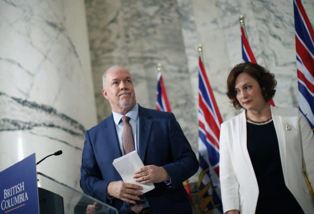 Premier John Horgan is joined by Minister of Energy Michelle Mungall after giving the green light on continuing construction on the controversial Site C Dam project during a press conference in Victoria on Dec. 11, 2017.