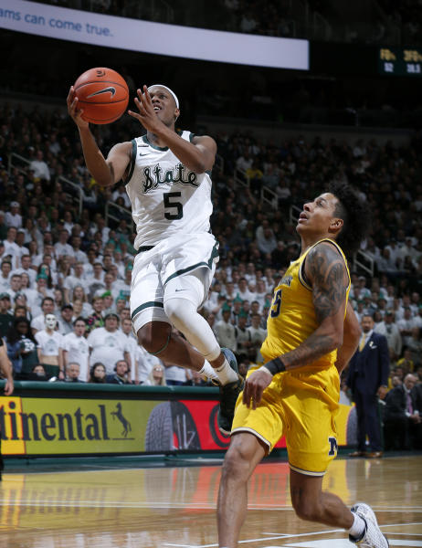 Michigan State's Cassius Winston, left, goes up for a layup against Michigan's Eli Brooks during the second half of an NCAA college basketball game, Sunday, Jan. 5, 2020, in East Lansing, Mich. (AP Photo/Al Goldis)