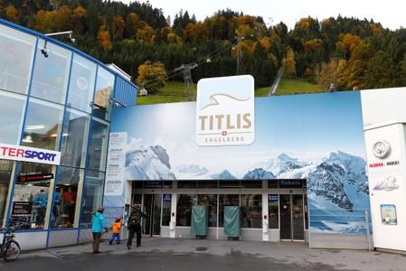 FILE PHOTO: Skiers walk in front of the lower terminus of the Titlisbahnen cablecar in Engelberg