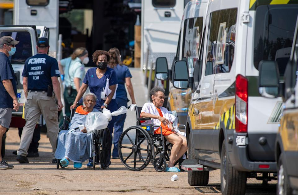 Paramedics evacuate people at a mass shelter Thursday in Independence, La., after Hurricane Ida blew through the area.