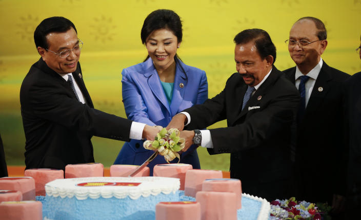 Chinese Premier Li Keqiang, left, joins his hand with Thai Prime Minister Yingluck Shinawatra, second from left, Brunei Sultan Hassanal Bolkiah, 2nd from right, for a cake cutting ceremony to mark the 10th anniversary of ASEAN-China strategic Partnership for Peace and Prosperity as Myanmar President Thein Sein looks on before the 16th Association of Southeast Asian Nations (ASEAN) - China Summit in Bandar Seri Begawan, Brunei, Wednesday, Oct. 9, 2013. (AP Photo/Vincent Thian)