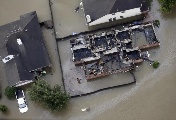 <p>A burned out home is surrounded by floodwaters from Tropical Storm Harvey on Tuesday, Aug. 29, 2017, in Spring, Texas. (Photo: David J. Phillip/AP) </p>