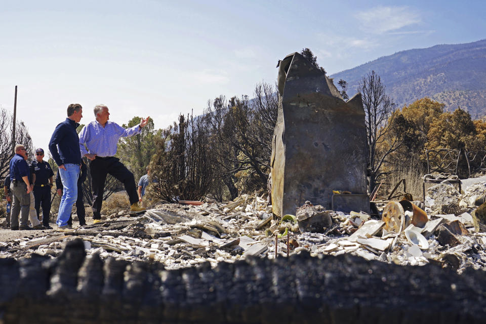 California Gov. Gavin Newsom, front left, and Nevada Gov. Steve Sisolak tour homes destroyed by wildfires near where the Tamarack Fire ignited earlier in July in Gardnerville, Nev., Wednesday, July 28, 2021. The governors of California and Nevada are calling for increased federal assistance as they tour an area blackened by one of several massive wildfires that have destroyed dozens of homes. Wednesday's tour of the Tamarack Fire along the state line comes as numerous wildfires char land and homes in a dozen states. (AP Photo/Sam Metz)