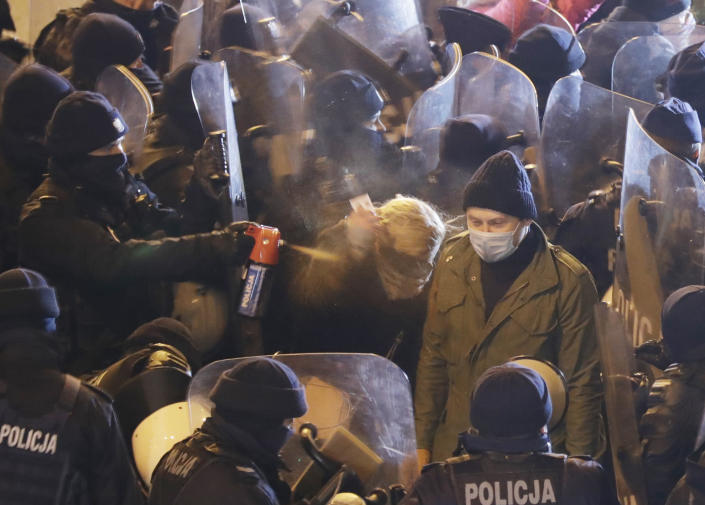 Police use tear gas against an opposition lawmaker, Barbara Nowacka, as protesters block a major thoroughfare in Warsaw, Poland, Saturday Nov. 28, 2020. The police blocked protesters from marching in Warsaw as demonstrations took place across Poland against an attempt to restrict abortion rights and recent use of force by police.(AP Photo/Czarek Sokolowski)