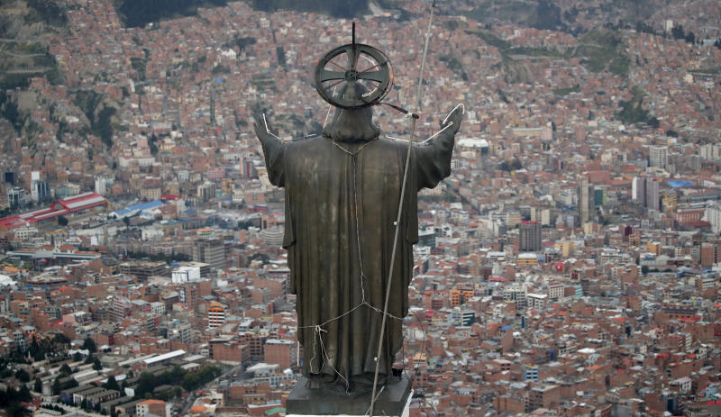 In this picture taken Tuesday, Jan. 7, 2020, a Christ statue overlooks El Alto, a city adjoining the capital city La Paz, Bolivia. Ancestral indigenous practices became more visible during the presidency of Evo Morales, who recognized the Andean earth deity Pachamama. While Bolivians are divided on former President Morales' legacy, the interim President Jeanine Añez wants to make the Bible front and center in public life. (AP Photo/Natacha Pisarenko)