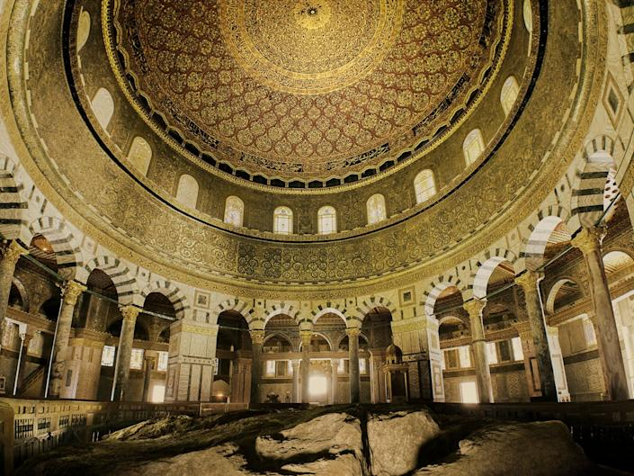 "A rare view of the rock at the center of the Dome of the Rock. Muslims refer to it as ""as-Sakrah"", the rock from where they believe the Prophet Muhammad ascended to heaven. In Jewish tradition, it known as ""the Foundation Stone,"" where Abraham prepared to sacrifice his son and where the Temples stood. Many historians believe the biblical Jebusites worshiped here nearly 5000 years ago."