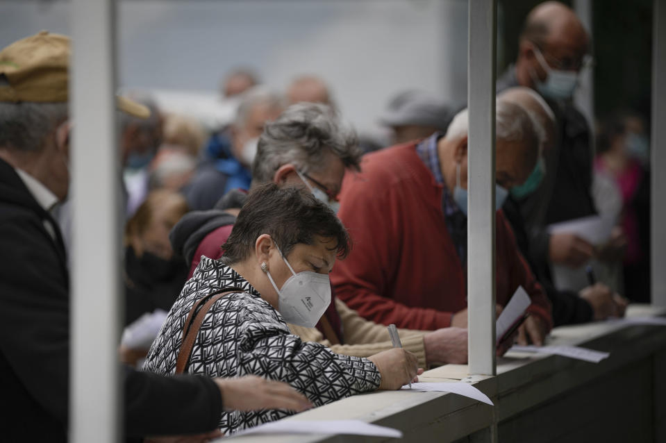 People fill out forms before getting the third dose booster Pfizer vaccine shot at the Matei Bals hospital in Bucharest, Romania, Tuesday, Sept. 28, 2021. Romania reported 11049 new COVID-19 infections in the past 24 hour interval, the highest ever daily number since the start of the pandemic. (AP Photo/Vadim Ghirda)