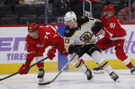 Detroit Red Wings defenseman Madison Bowey (74) and Boston Bruins center Charlie Coyle (13) chase the puck during the third period of an NHL hockey game, Friday, Nov. 8, 2019, in Detroit. (AP Photo/Carlos Osorio)