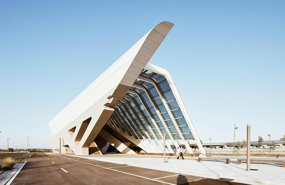 "Designed by Zaha Hadid Architects in 2017, the Afragola station sits on the outskirts of <a href=""https://www.cntraveler.com/story/how-to-spend-24-hours-in-naples-according-to-a-local?mbid=synd_yahoo_rss"" rel=""nofollow noopener"" target=""_blank"" data-ylk=""slk:Naples"" class=""link rapid-noclick-resp"">Naples</a> and serves high-speed and intercity train passengers and commuters from the region. From above, the concrete and steel station looks like a trapezoidal snake crawling along the Italian countryside. It's long curving shape actually serves as a walkway, though, connecting the two communities on either side of the tracks, in addition to providing space for shops, restaurants, and other amenities for train travelers."