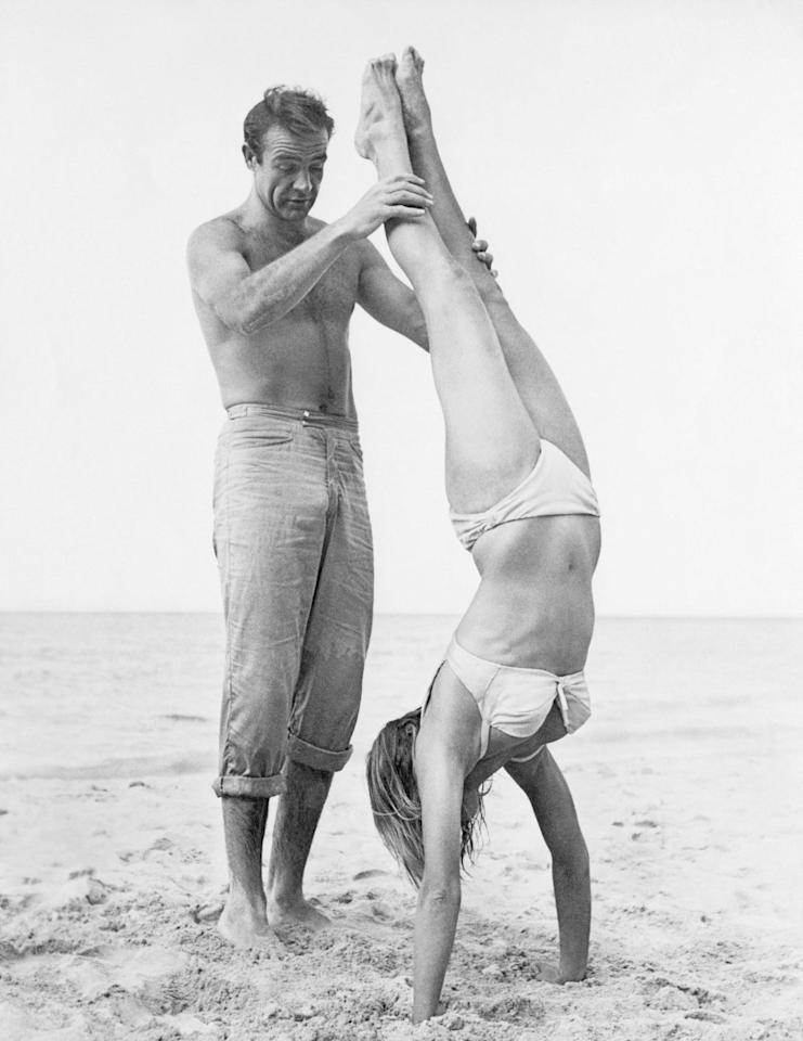 <p>Sean Connery holds Ursula Andress while she does a handstand on a beach in a white bikini on the set of the film <em>Dr. No</em>.</p>