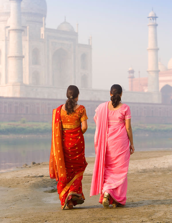 Women walk near the Taj Mahal. (Photo: Stocksy)
