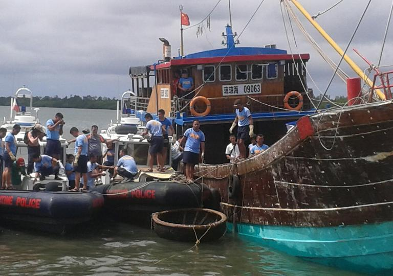 Philippine maritime police unload some of the sea turtles from a Chinese-flagged vessel (R) seized by officials off the disputed Half Moon Shoal, west of Palawan, on May 11, 2014