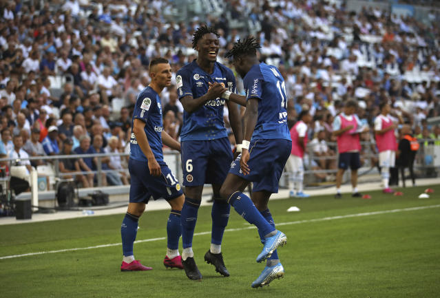 Reims' Boulaye Dia, right, celebrates with Axel Disasi, center, after scoring the opening goal during the French League One soccer match between Marseille and Reims at the Velodrome Stadium in Marseille, France, Saturday, Aug. 10, 2019. (AP Photo/Daniel Cole)