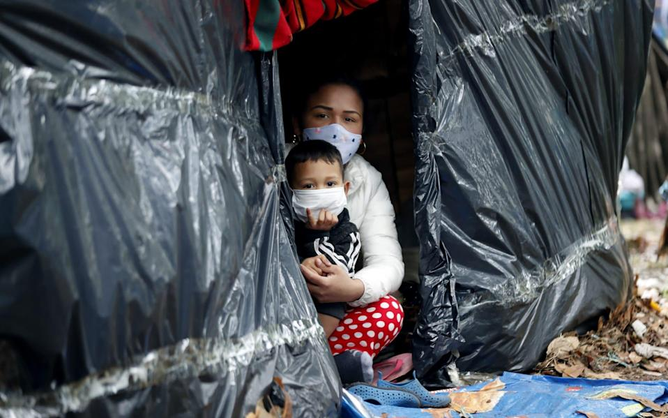 Venezuelan citizens remain in a makeshift camp set on the separator of the northern highway, in Bogota, Colombia - Mauricio Duenas Castaneda/Shutterstock