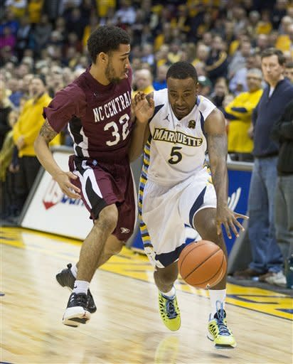 Marquette's Junior Cadougan (5) drives past North Carolina Centrals' Emmanuel Chapman during the first half of an NCAA college basketball game, Saturday, Dec. 29, 2012, in Milwaukee. (AP Photo/Tom Lynn)