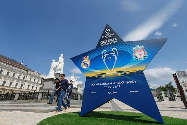 People walk pass an installation with the logo of the UEFA Champions League final in central Kiev, Ukraine May 12, 2018. REUTERS/Valentyn Ogirenko