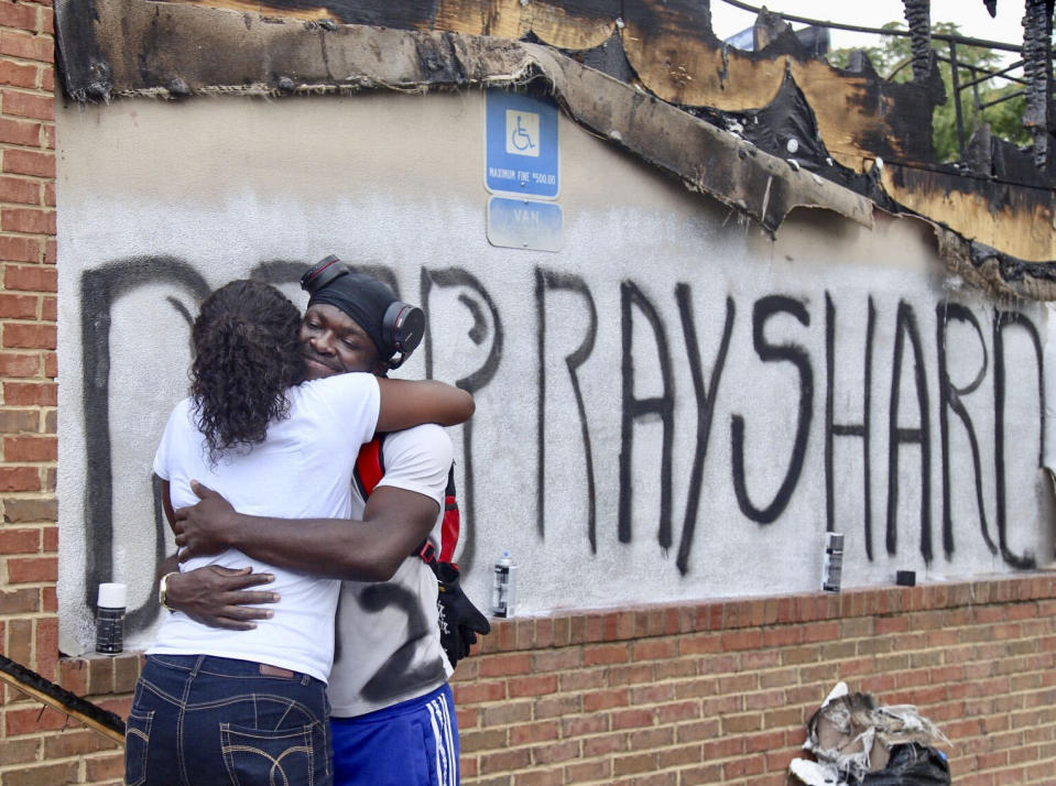 Eva Snow and Joseth Jett hug Sunday, June 14, 2020, after Jett spray painted over the top of graffiti from the night before and painted RIP Rayshard. On Saturday, protestors set fire to the Atlanta Wendy's where Rayshard Brooks, a 27-year-old black man, was shot and killed by Atlanta police Friday evening during a struggle in a Wendy's drive-thru line. (Steve Schaefer/Atlanta Journal-Constitution via AP)