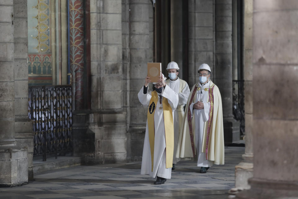 Notre Dame rector Patrick Chauvet leads a procession, wearing protective helmets, as part of Maundy Thursday ceremony, in Notre Dame Cathedral, Thursday, April 1, 2021, almost two years after a massive fire ravaged the Gothic cathedral. (AP Photo/Christophe Ena, Pool)